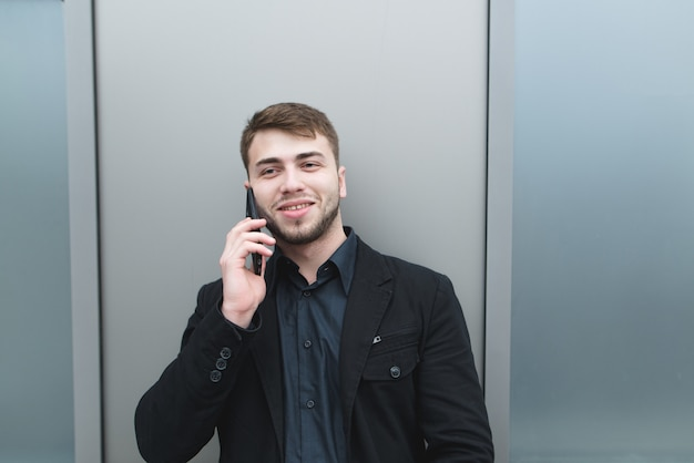 Een positieve man in een pak en een baard spreekt telefonisch op een metalen wand en glimlacht.