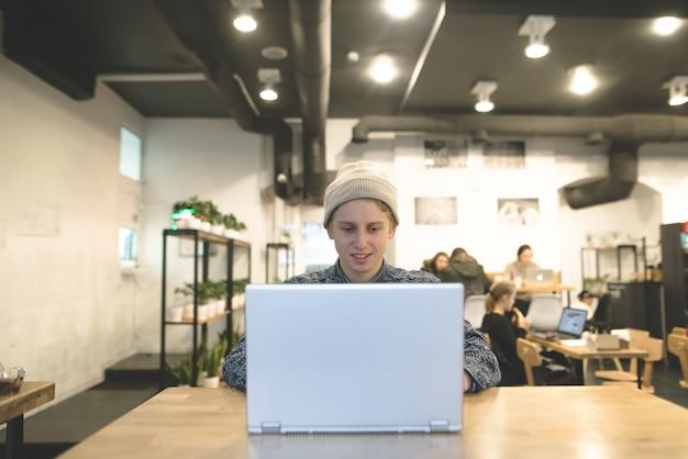 Een positieve student geniet van een laptop in een gezellig café. de stijlvolle hipsters werken achter de computer in het café.