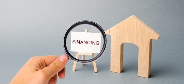 Een poster met het woord financiering en een houten huis. aantrekken van investeringen in woningen