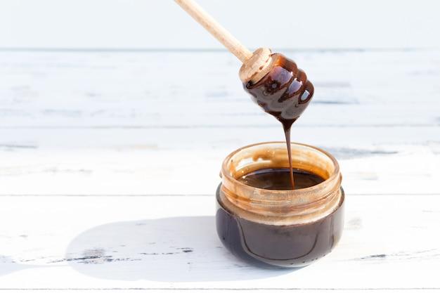 Een pot chocolade dessert, honing of cosmetische masker op witte houten tafel