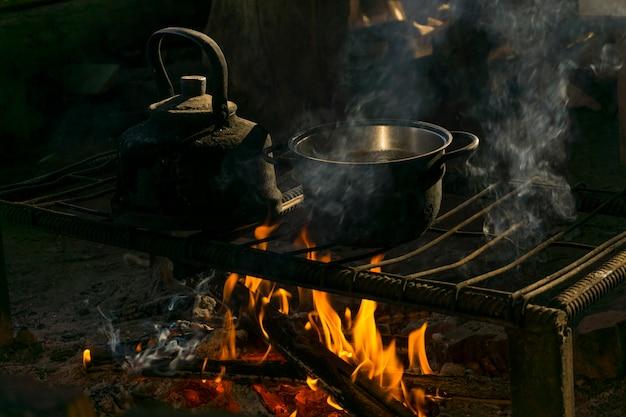 Een pot en een ketel staan boven een vuur op een draagbare haard gemaakt van metalen staven in een nomadenwoning