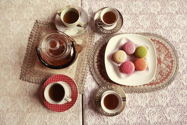 Een pot en een kopje thee met macaroon