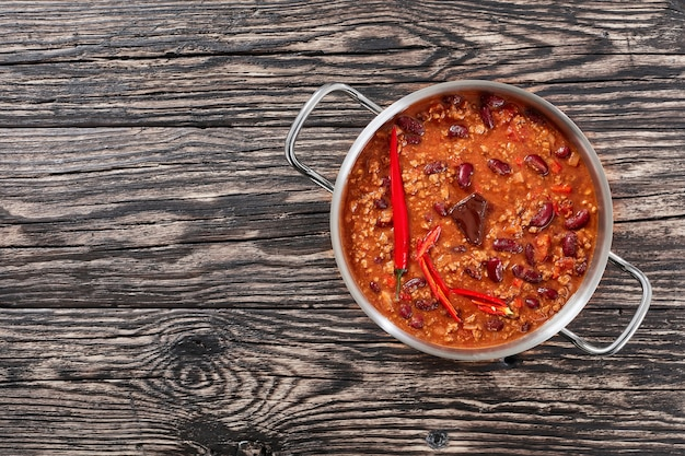 Een pot hete heerlijke chili con carne met hele roodgloeiende chilis, bruine bonen, tomaten en een stuk chocolade