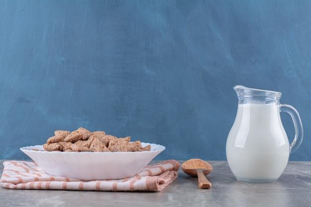 Een pot melk met een wit bord vol gezonde granen.