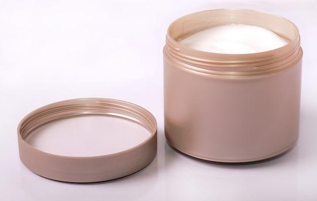 Een pot met stylingcrème voor mannen op een witte ondergrond