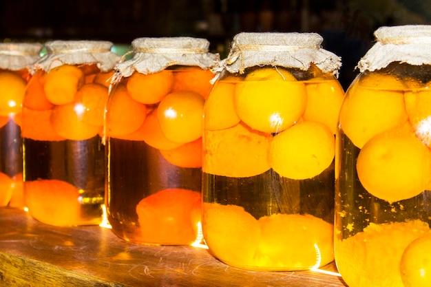 Een pot perziken op een donkere achtergrond. ingeblikt fruit in grote glazen potten op een houten plank