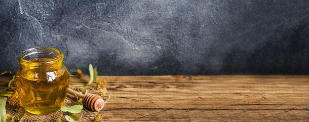 Een pot vloeibare honing van lindebloemen en een stok met honing kopieer de ruimte