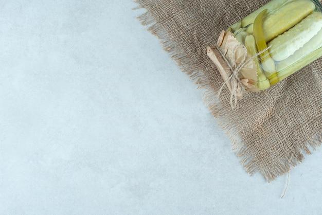 Een pot zelfgemaakte ingelegde komkommers op jute.