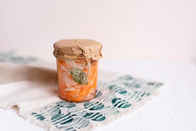 Een pot zuurkool en wortelen in zijn eigen sap met kruiden, witte houten tafel. traditioneel huisgemaakt