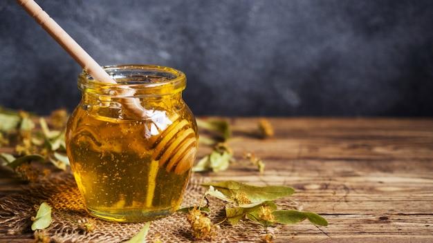 Een potje vloeibare honing van linden bloemen en een stokje met honing op een donkere achtergrond. kopieer ruimte