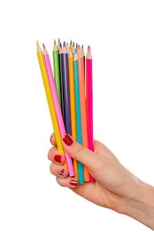 Een potlood van de vrouwenhand houdt kleurenkleur (kleurrijk) zoals een regenboog op het witte bureau