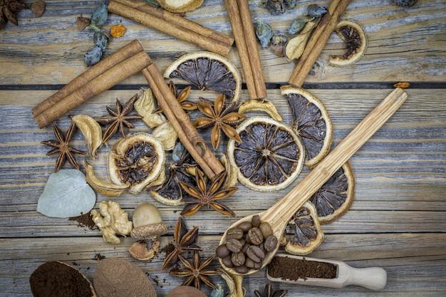 Een prachtig arrangement van gedroogde citroenen, kaneel, koffie op houten lepels op hout