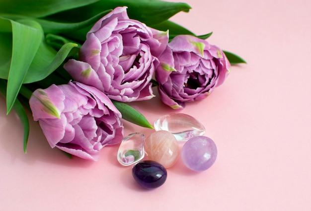 Een prachtig boeket lila tulpen in volle bloei met natuurstenen van amethist, rozenkwarts en bergkristal