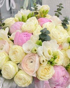Een prachtig boeket van delicate bloemen. witte rozen gecombineerd met roze pioenrozen, ranonkels en lentefresia.