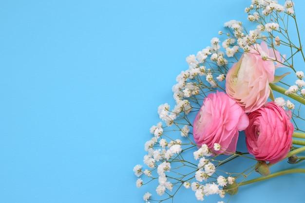 Een prachtig boeket van roze ranonkels (boterbloemen) met delicate witte gipskruidbloemen op een blauwe ondergrond