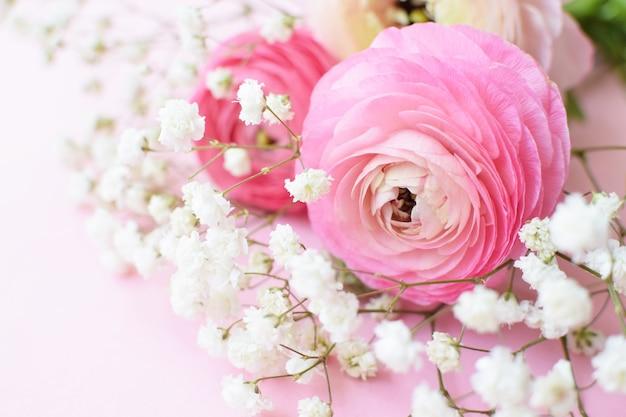 Een prachtig boeket van roze ranonkels (boterbloemen) met delicate witte gipskruidbloemen op een roze ondergrond