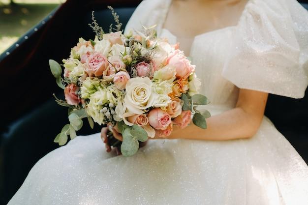 Een prachtig bruidsboeket met rozen in de handen van de bruid