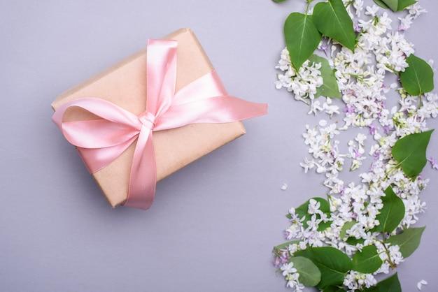 Een prachtig cadeau met een satijnen lint tegen de achtergrond van lila bloemen.