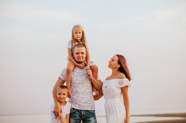 Een prachtig gezin met twee kinderen in lichte kleren poseren en glimlachen op de zanderige kust