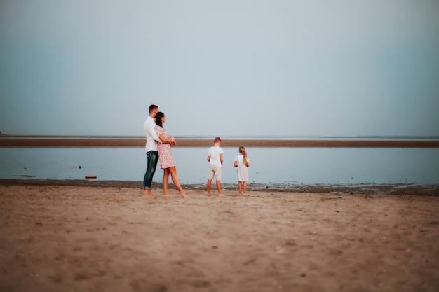 Een prachtig gezin met twee kinderen in lichtgekleurde kleding poseren achter op de zandige kust
