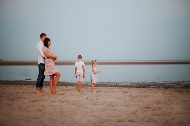 Een prachtig gezin met twee kinderen in lichtgekleurde kleren poseren achterin en glimlachen op de zandige kust