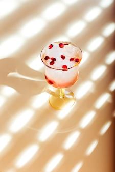 Een prachtig glas iced tonic water met granaatappel, tegenlicht, mooie schaduwen en reflecties op het oppervlak