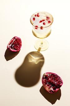 Een prachtig glas ijskoud tonisch water met granaatappel, hard tegenlicht, diepe schaduwen