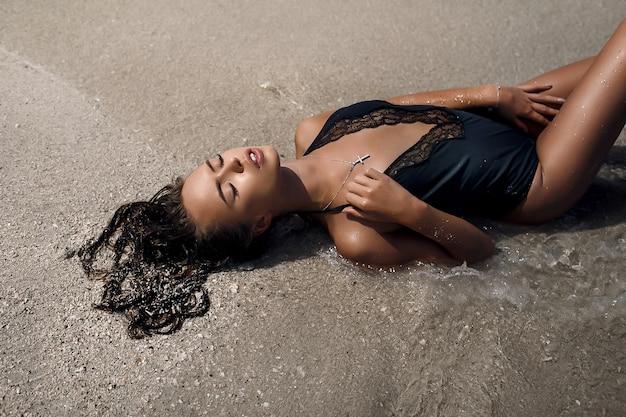 Een prachtig jong model met gesloten ogen in een zwart zwempak uit één stuk ligt op het zand bij de zee