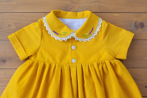 Een prachtig kinderjurkje van naturel katoen met borduursel van paarse bloemen op de kraag. kant aan de kraag. kinderkleding. een jurk voor een meisje.