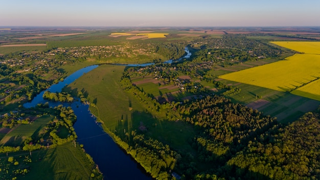 Een prachtig landschap van een geel veld en een groen bos en een rivier
