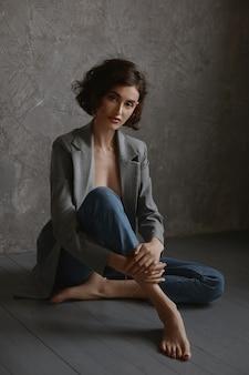 Een prachtig modelmeisje met een slank lichaam in een spijkerbroek en een verleidelijk topje zit binnenshuis op de vloer