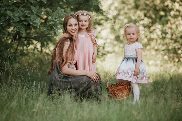 Een prachtig portret van moeder met twee dochters in het park.