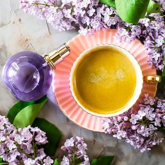 Een prachtig stilleven van lila, een kopje koffie en een vrouwelijke parfumfles