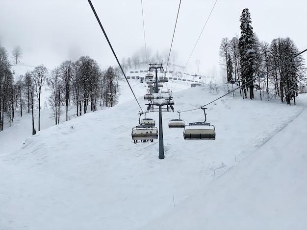 Een prachtig uitzicht naar de cabines van de skilift door de mist in de bergen