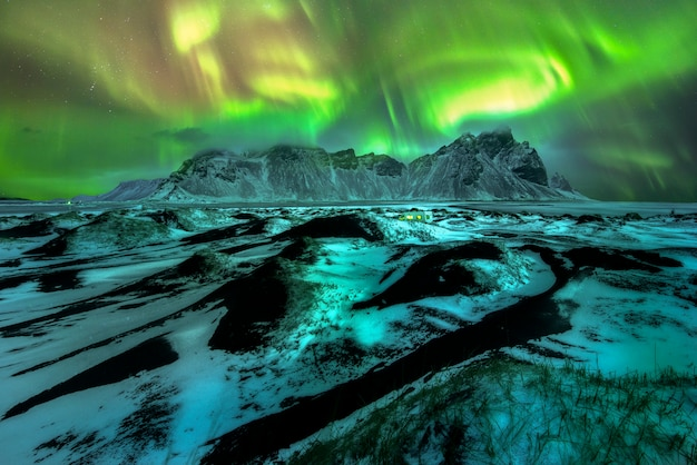 Een prachtige groene en rode aurora die over de vestrahorn, ijsland danst
