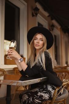 Een prachtige jonge vrouw in een zwarte hoed, genietend van een glas wijn en kijkend naar de cafétafel op straat op een zomeravond.