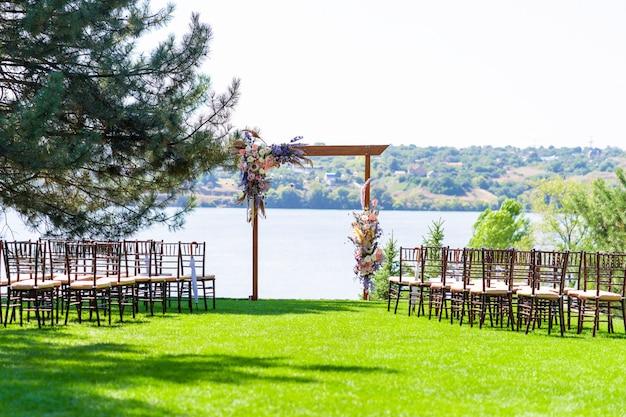 Een prachtige locatie voor een openlucht huwelijksceremonie. huwelijksboog en rijen van gaststoelen op een groen gazon met uitzicht op de rivier