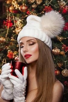 Een prachtige nieuwjaarsfoto. een mooi meisje in een hoed en wanten houdt een rode mok vast