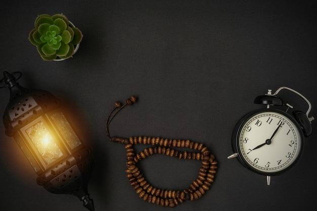 Een prachtige ramadan kaars lantaarn en rozenkrans kralen met een kopie ruimte op zwarte achtergrond