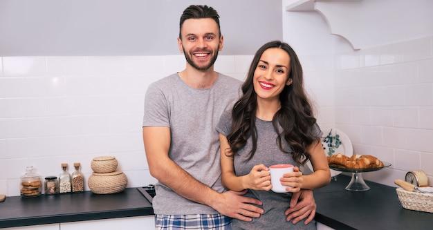 Een prachtige vrouw in pyjama knuffelt haar gelukkige echtgenoot terwijl ze op een aanrecht in de keuken zit, beiden glimlachen met hun ogen dicht.