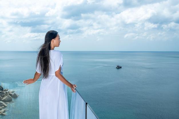 Een prachtige vrouw met lang zwart haar staat op een transparant terras