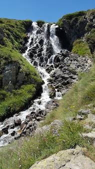 Een prachtige waterval in de bergen in de zomer