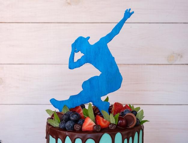 Een prachtige zelfgemaakte cake met groene kaascrème, aardbeien en kersenbessen, versierd met een figuur van een danseres in een hoed
