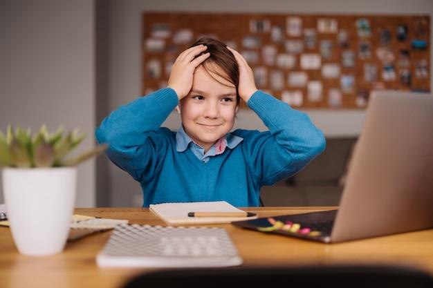 Een preteen-jongen die de online lessen beu is