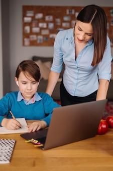 Een preteen-jongen gebruikt een laptop om een videogesprek te voeren met zijn leraar naast zijn moeder