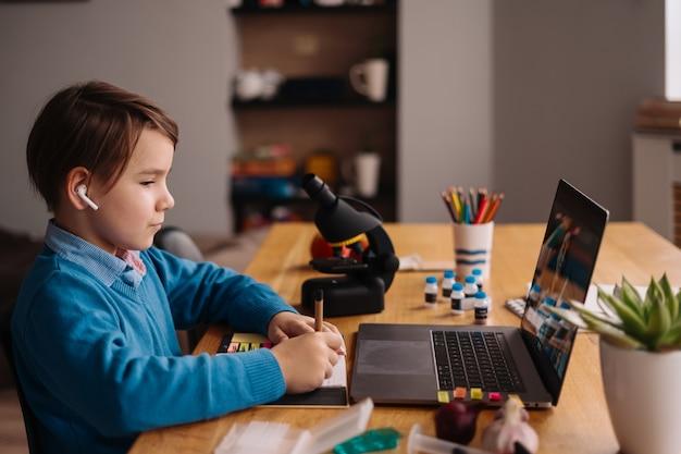 Een preteen-jongen gebruikt een laptop om een videogesprek te voeren met zijn leraar