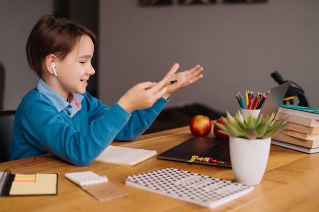 Een preteen-jongen gebruikt een laptop om online lessen te geven