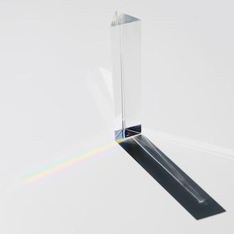 Een prisma dat zonlicht verdeelt dat in een spectrum op een witte achtergrond verdeelt