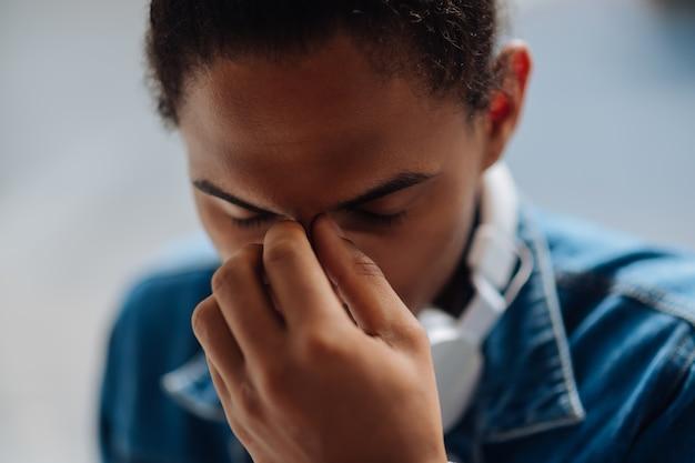 Een probleem hebben. geconcentreerde brunette man houdt ogen gesloten tijdens pauze