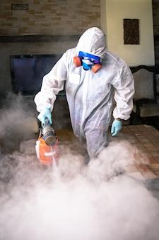 Een professional desinfecteert de kamer met een antisepticum